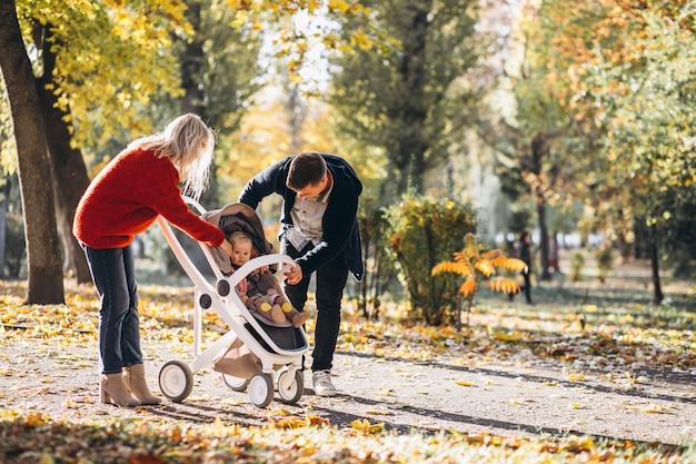 Familia con hija en un cochecito caminando por un parque de otoño