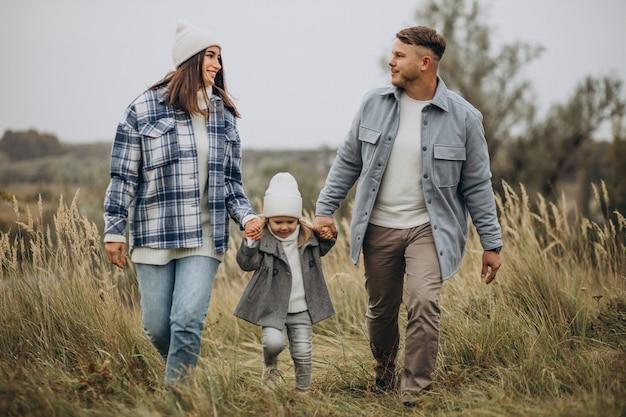 Familia con hija pequeña juntos en clima otoñal divirtiéndose