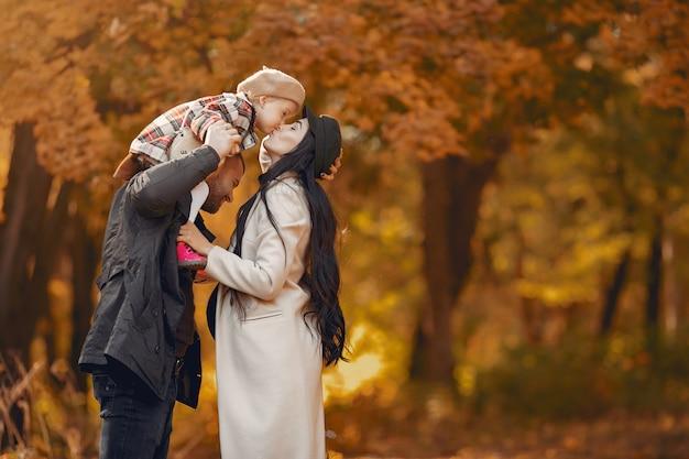 Familia con hija pequeña en un parque de otoño