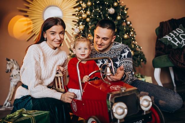 Familia con hija pequeña con regalo de navidad por árbol de navidad