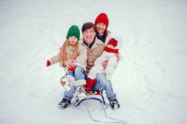 Familia con hijas lindas en un parque de invierno