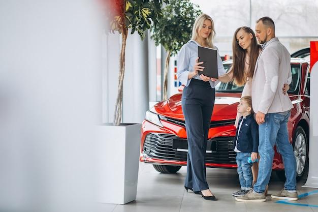 Familia con hijo elegir un coche en una sala de exposición de coches