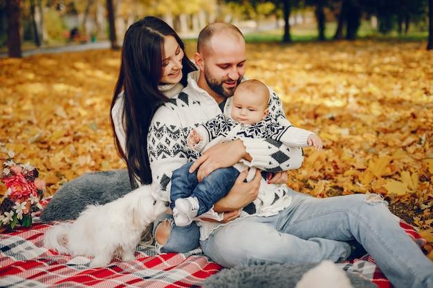 Familia con hijo en un parque de otoño