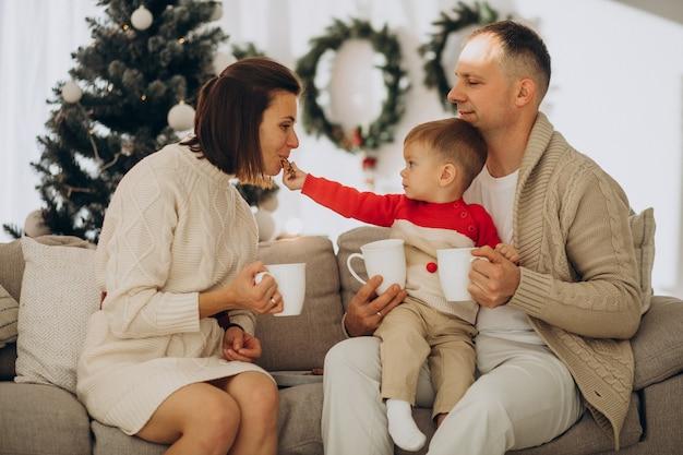 Familia con hijo pequeño en navidad por árbol de navidad en casa