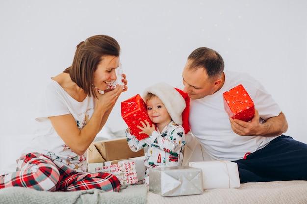 Familia con hijo pequeño y regalos de navidad acostado en la cama