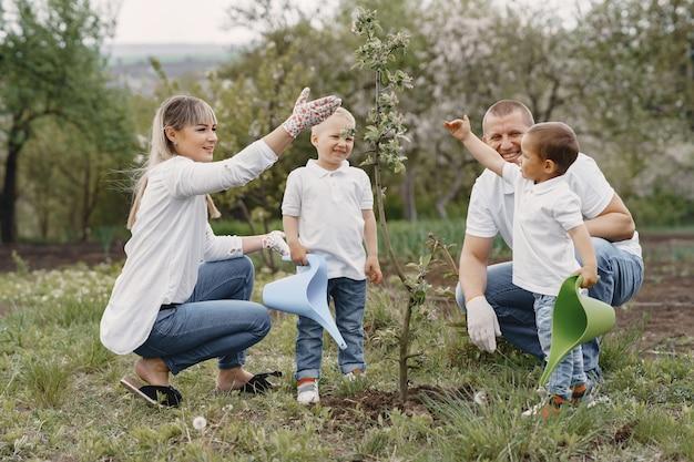 Familia con hijos pequeños están plantando un árbol en un patio