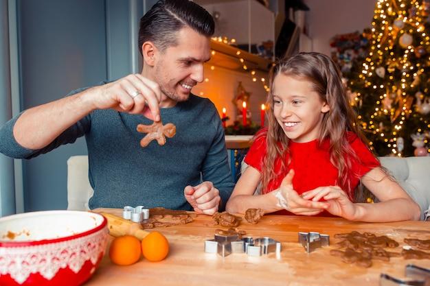 Familia horneando galletas de jengibre en vacaciones de navidad