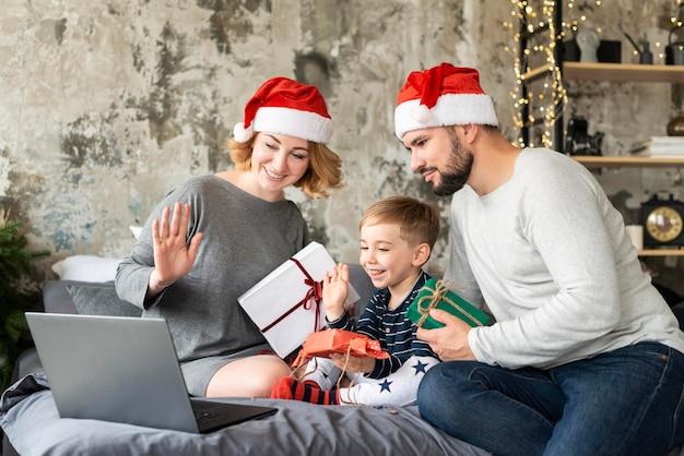 Familia intercambiando regalos mientras videollamadas a familiares en navidad