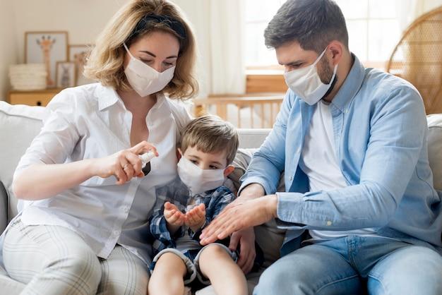 Familia en interiores usando desinfectante y usando máscaras médicas