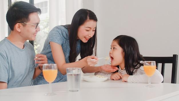 Familia japonesa asiática desayuna en casa. asia feliz papá, mamá e hija comen espaguetis beben jugo de naranja en la mesa en la cocina moderna en casa por la mañana.