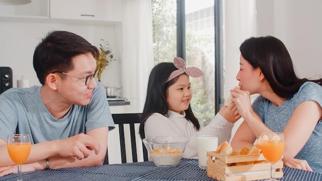 Familia japonesa asiática desayuna en casa. asia mamá, papá e hija se sienten felices hablando juntos mientras comen pan, cereales y leche en un tazón sobre la mesa en la cocina por la mañana.