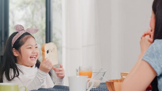 Familia japonesa asiática desayuna en casa. la hija asiática escoge y juega la sonrisa de risa del pan con los padres mientras come cereal de cereales y leche en un tazón sobre la mesa en la cocina moderna en la mañana.