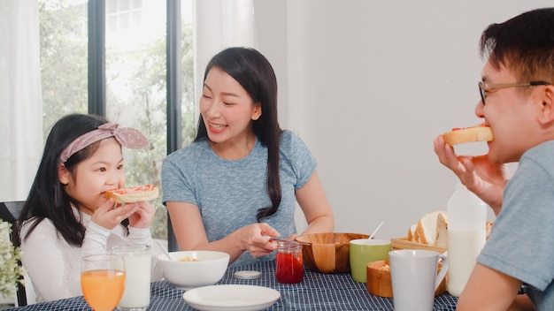 Familia japonesa asiática desayuna en casa. la mamá feliz asiática que hace la mermelada de fresa en el pan para la hija come cereal y leche de las avenas en cuenco en la tabla en la cocina en la mañana.