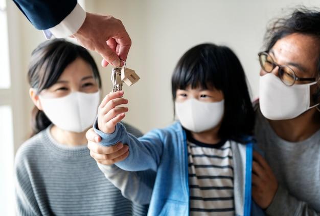 Familia japonesa en mascarilla comprando una casa nueva