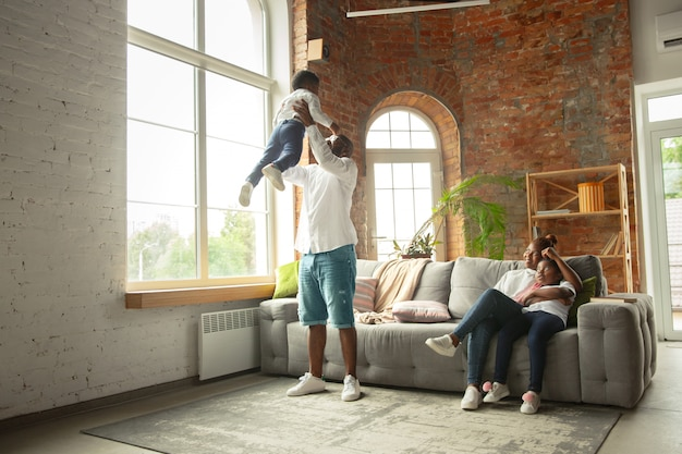 Familia joven y alegre durante la cuarentena, aislamiento pasando tiempo juntos en casa.