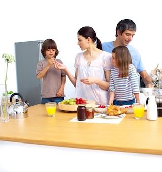 Familia joven alegre desayunando