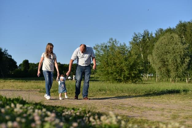 Familia joven amigable con niños descansando en el verano en la naturaleza.