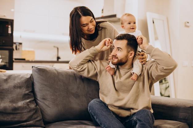 Familia joven con bebé niña pequeña en casa sentado en el sofá