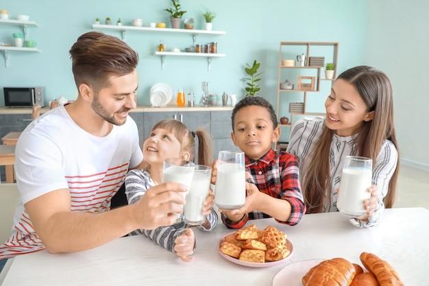 Familia joven bebiendo leche sabrosa en la cocina de casa