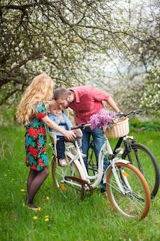 Familia joven en una bicicleta en el jardín de primavera