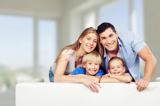 Familia joven en casa sonriendo a la cámara