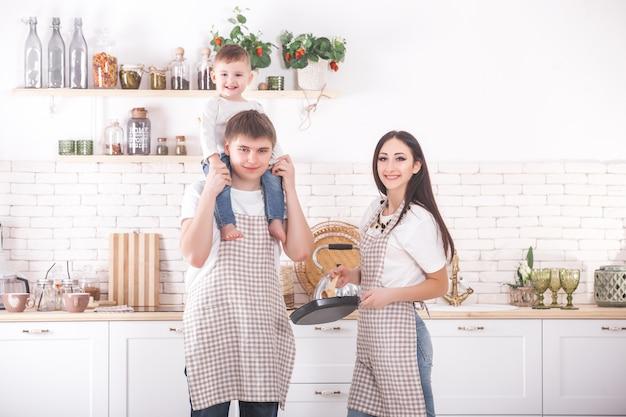 Familia joven cocinando juntos. marido, mujer y su pequeño bebé en la cocina. familia amasando la masa con harina. la gente cocina la cena o el desayuno.