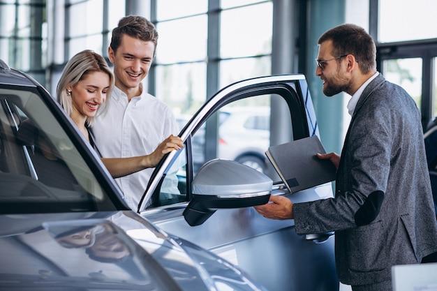 Familia joven comprando un automóvil en una sala de exposición de automóviles