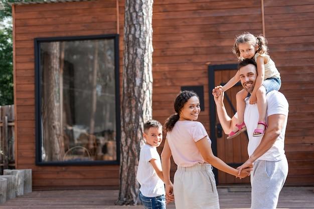 La familia joven consume la espalda, mirando a la cámara, posando cerca de la casa de madera, están felices de sus vacaciones de verano fuera de la ciudad, la niña está sentada sobre los hombros de su padre