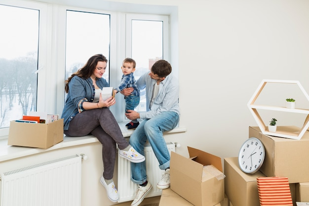 Familia joven descansando en su nuevo hogar con cajas de cartón en movimiento.