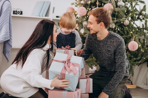 Familia joven desempacando regalos con pequeño hijo por árbol de navidad
