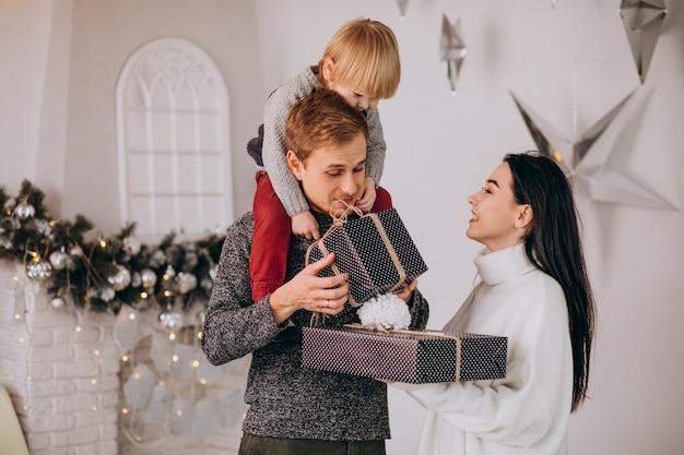 Familia joven desempacando regalos con pequeño hijo en navidad