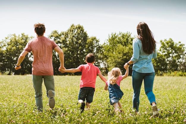 Familia joven despreocupada corriendo por un prado