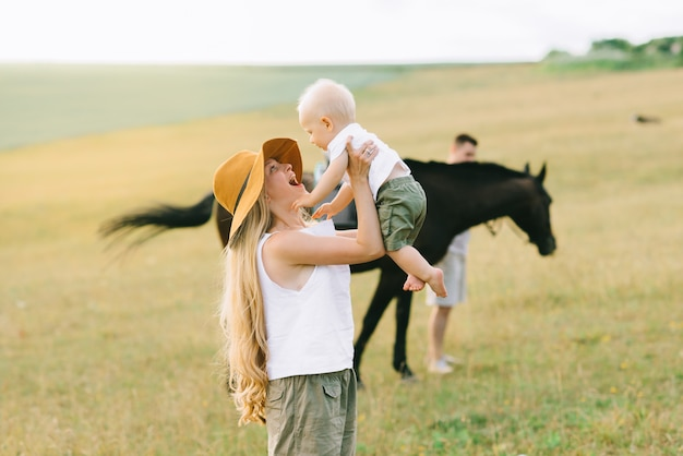 Una familia joven se divierte en el campo. padres e hijo con un caballo.