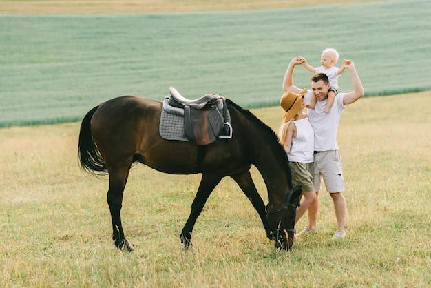 Una familia joven se divierte en el campo. padres e hijos con un caballo