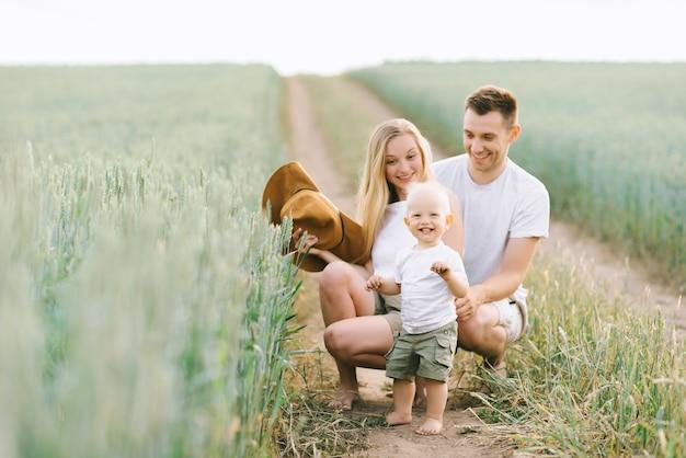 Una familia joven se divierte con su pequeño bebé en el campo