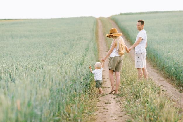 Una familia joven se divierte con su pequeño bebé en el campo.