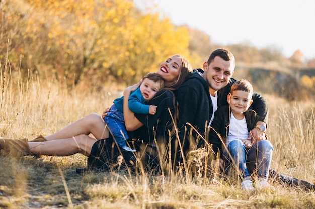 Familia joven con dos hijos juntos sentados en el parque