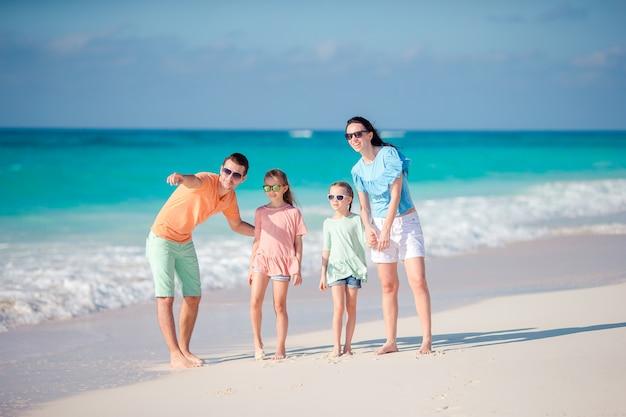 Familia joven con dos hijos en vacaciones en la playa