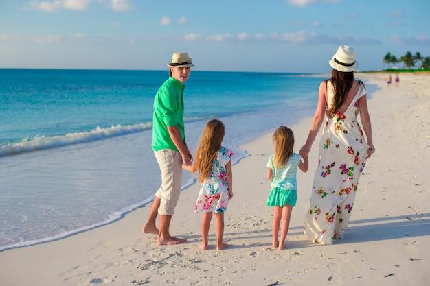 Familia joven con dos hijos en vacaciones tropicales en la noche