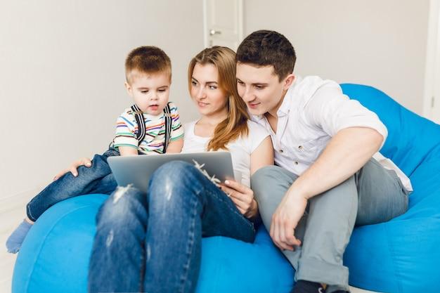 Familia joven de dos padres y un niño se sientan en sillas de saco azul.