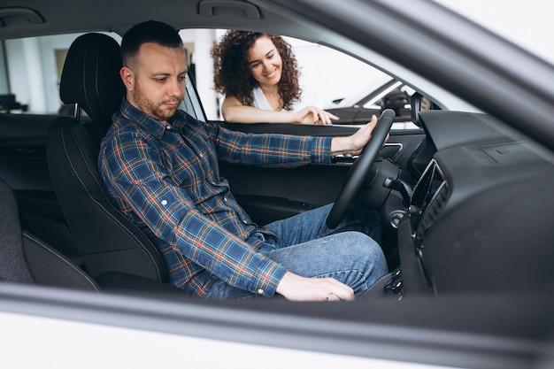 Familia joven eligiendo un automóvil en una sala de exposición de automóviles