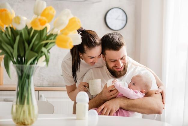 Familia joven feliz alimentación infantil en la cocina
