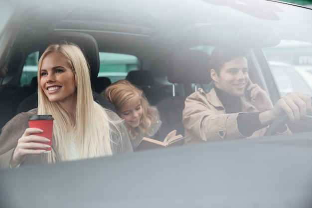 Familia joven feliz en auto