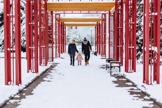 La familia joven feliz camina con el bebé en la calle del invierno, mamá, papá, niño