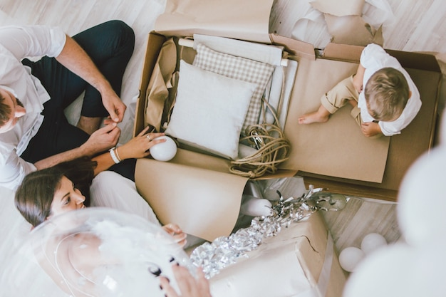 Familia joven feliz celebra el primer año del bebé y desempaca regalos en casa en un interior brillante, vista desde arriba