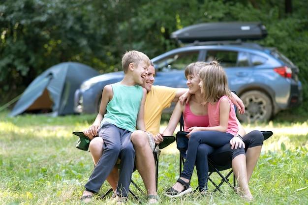 Familia joven feliz disfrutando de tiempo en capmsite al aire libre. los padres y sus hijos sentados juntos y hablando alegremente.