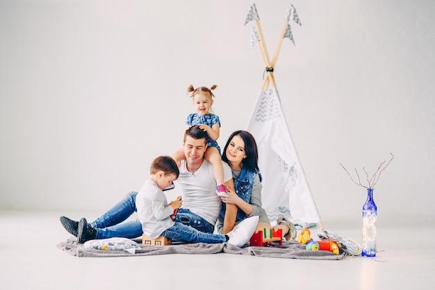 Familia joven feliz divirtiéndose en la habitación de los niños blancos. madre, padre, hermana y hermano jugando juntos.