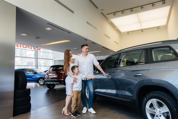 Una familia joven y feliz elige y compra un automóvil nuevo en un concesionario de automóviles. comprar un auto nuevo.