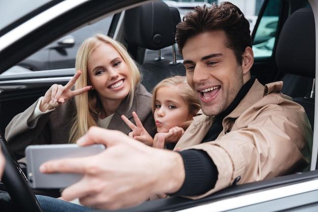 Familia joven feliz hacer selfie por teléfono móvil.