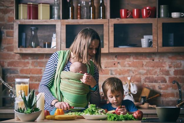 Familia joven feliz, hermosa madre con dos hijos, adorable niño preescolar y bebé en honda cocinando juntos en una cocina soleada.